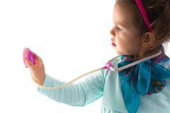 Young child girl with a phonendoscope playing doctor. Healthcare and medicine concept. Stock Images