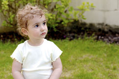 Young child, girl, in plain light top daydreaming. Stock Photography