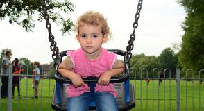 Young child, girl, playing on a swing at the playground. A young girl, toddler, is on a swing the playground in the park. She is wearing a pink top and blue Royalty Free Stock Image