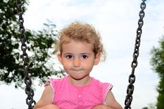 Young child, girl, playing on a swing at the playground. A young girl, toddler, is on a swing the playground in the park. She is wearing a pink top and has Stock Photo