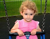 Young child, girl, playing on a swing at the playground. A young girl, toddler, is on a swing the playground in the park. She is wearing a pink top and has Royalty Free Stock Images