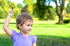 Young child, girl, toddler, holding a feather high as she plays in the park. Royalty Free Stock Image