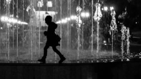 Young child girl walking the fountain border. Stylized as black and white silhouette stock image