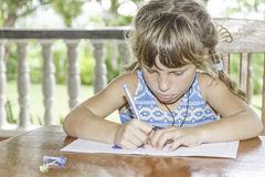Young child girl writing in notebook, outdoors portrait, educati Stock Photos