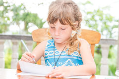 Young child girl writing in notebook, outdoors portrait, educati Royalty Free Stock Photography