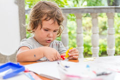 Young child girl writing in notebook, outdoors portrait, educati Royalty Free Stock Images