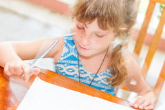 Young child girl writing in notebook, outdoors portrait, educati Stock Image