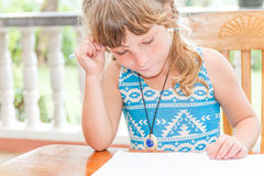 Young child girl writing in notebook, outdoors portrait, educati Stock Photo