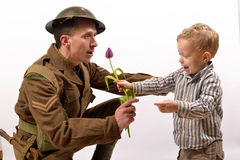 A young child gives a flower to a British soldier Stock Images