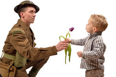 A young child gives a flower to a British soldier Royalty Free Stock Photos