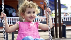 Young child having fun on a swing. Royalty Free Stock Photo