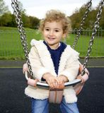 Young child having fun on a swing. Royalty Free Stock Image