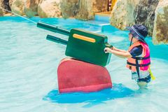Young child having fun with water cannon in aqua park Royalty Free Stock Photo