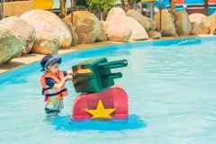 Young child having fun with water cannon in aqua park Royalty Free Stock Photos