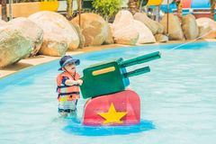 Young child having fun with water cannon in aqua park Stock Photography