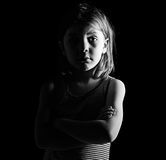 Young Child with her Arms Crossed. Low Key Shot of a Young Child with her Arms Crossed Royalty Free Stock Image