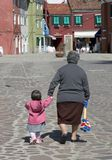 A young child and her grandmother walk along the streets of Bura Royalty Free Stock Image