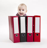 Young child hiding behind ring file Stock Image