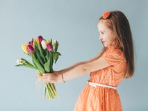 Young child holding a bunch of fresh flowers. Young child holding a bunch of freshly cut flowers. Celebrating a birthday Royalty Free Stock Images