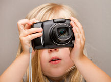 Young child holding a camera taking a picture Royalty Free Stock Images
