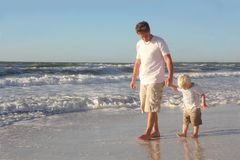 Young Child Holding Father's Hand While Walking in Ocean on Beach Royalty Free Stock Photo