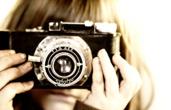 Young child holding old camera. To her face. Sepia Toned, shallow depth of field, focus on lens glass stock photos