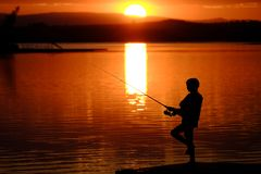 Young Child Kid Person Fishing in Lake or River Sunset stock photo
