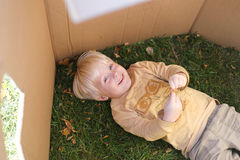 Young Child Laying in Grass while Playing in Cardboard Box Fort Royalty Free Stock Image