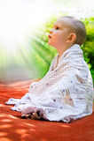 Young child looking in awe at the sun. Young child sitting draped in a blanket on an orange mat in the garden looking up in awe and wonderment at the rays of the Stock Photography