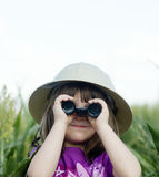 A young child looking through binoculars. While wearing a safari hat royalty free stock images