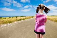 Young child looking down a long road Stock Photo