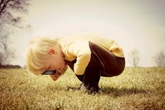 Young Child looking through Magnifying Glass. A young child is bending down looking in the grass, investigating something with a magnifying glass.  Vintage style Royalty Free Stock Photos