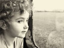 A young child looking out a window. Royalty Free Stock Photos