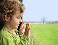 A young child looking out a window. Stock Photo