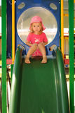 Young child looking sad on a playground slide