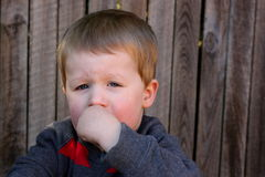 Young child looking upset. Young child sitting outside looking upset Stock Image