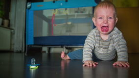 Young child lying on the floor a n crying for his mother. On this slow motion high quality footages is a little blue eyes baby boy lying on the wooden floor and stock video