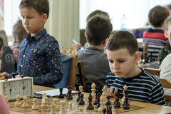 Young child making a move with a horse during a chess tournament at a school, with several other competitors in the background Royalty Free Stock Image