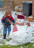 Young child making a snowman. Stock Photo