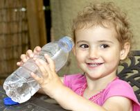 Young child outdoors drinking water from a bottle. Royalty Free Stock Images