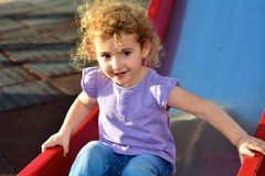 Young child outdoors having fun on a slide. Royalty Free Stock Photo