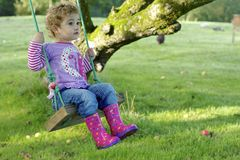 Young child outdoors having fun on a swing. Royalty Free Stock Image