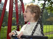 Young child outdoors having fun on a swing. Royalty Free Stock Photos