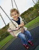 Young child outdoors having fun on a swing. Stock Photography