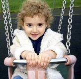 Young child outdoors having fun on a swing. Stock Images