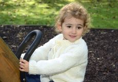 Young child outdoors having fun on a swing. Royalty Free Stock Photography