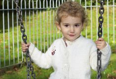 Young child outdoors having fun on a swing. Royalty Free Stock Images