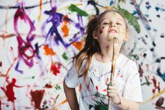 Young child painter standing with a brush. In front of a messy background. Creativity Stock Photo