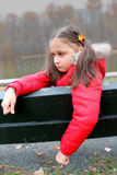 Young child with sad expression sitting on the bench. Young girl with sad expression, looking down. The girl has ponytails with yellow flower Stock Photo