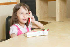 Young child on phone looking happy Stock Image